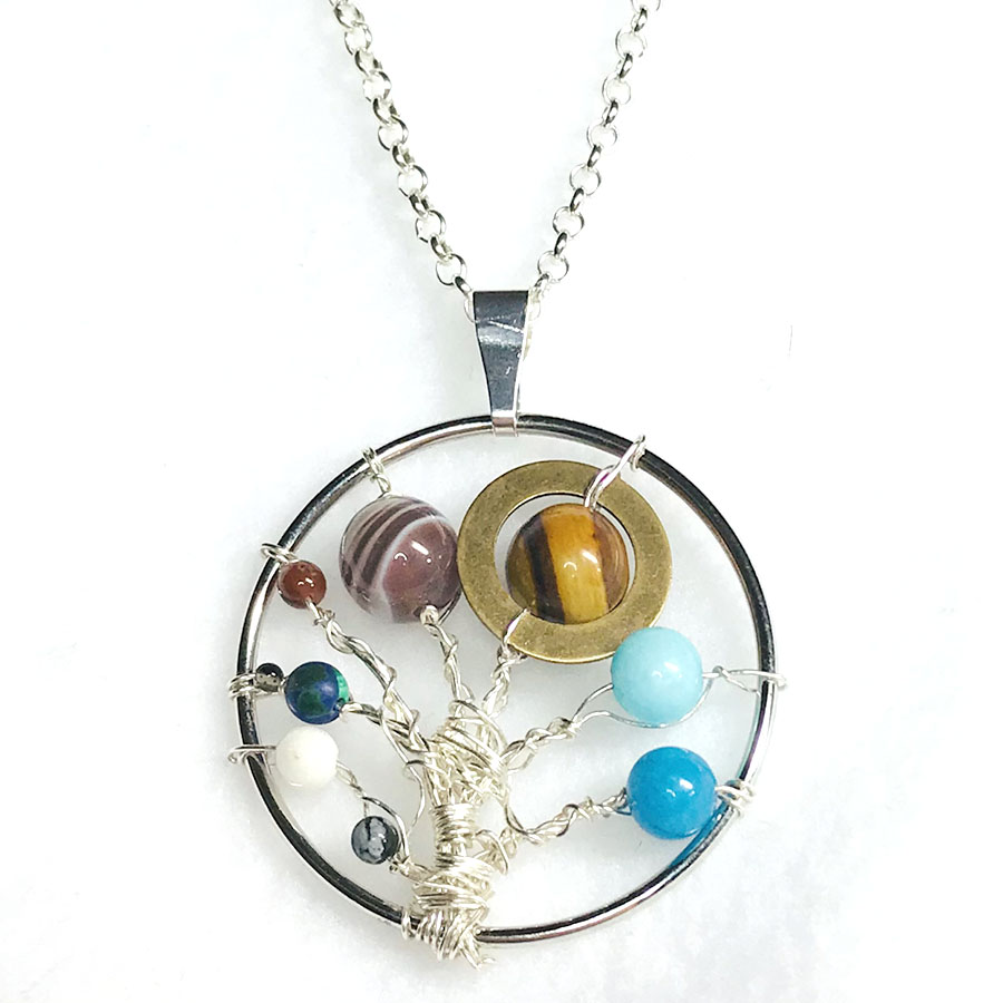 A ring-shaped pendant with wire and semiprecious beads wrapped onto it.